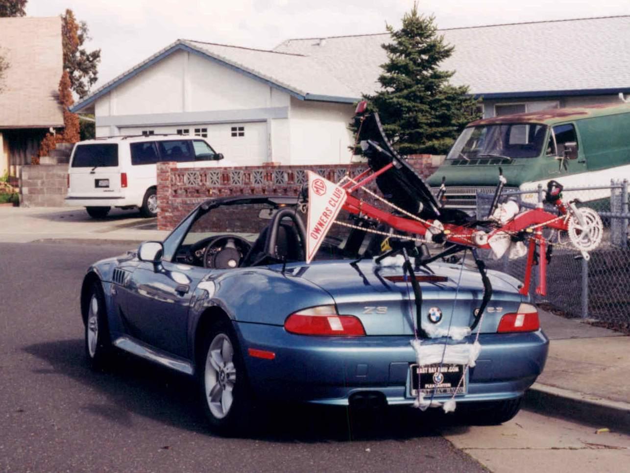 blue 2000 BMW Z3, top down, red Reynolds Wishbone recumbent frame on bike rack