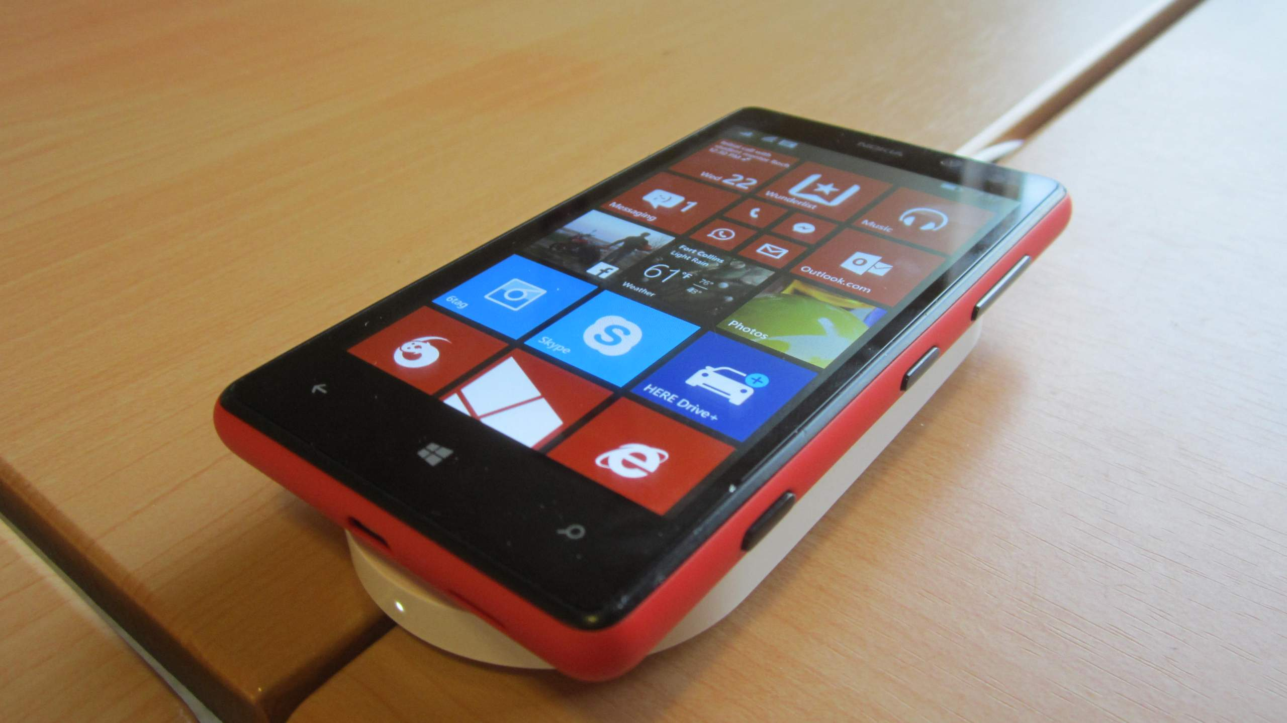 My Nokia Lumia 820 with a new red Qi charging cover on top of a white Nokia DT-900 charging pad.