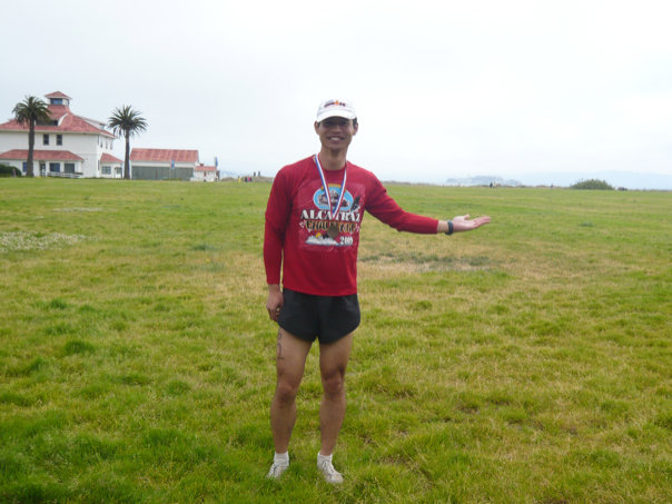 Felix Wong at Chrissy Field after the Alcatraz Challenge. You can see Alcatraz a little bit above my hand in the distance. (Photo: Alyssa U.)