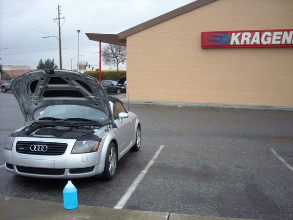 gallon of blue windshield washer fluid, silver 2001 Audi TT Roadster with hood up in parking lot of Kragen Auto Parts