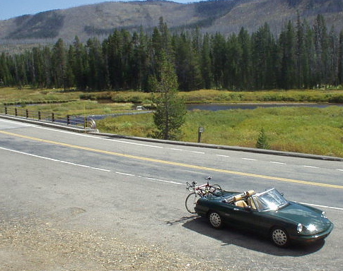 green 1991 Alfa Romeo Spider carrying a red bicycle, Yellowstone National Park
