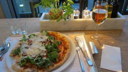 Enjoying a pizza with lots of vegetables and mozzarella in Vapiano.