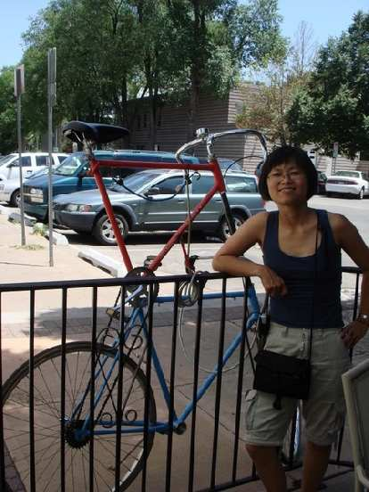 Stacey with a double-decker bicycle parked next to Jeju's.