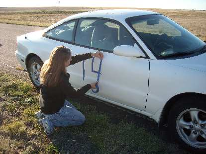 Kelly applying numbers to the right side of her car.