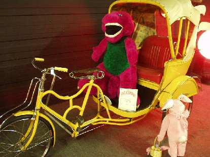 This is a Chinese rickshaw carrying Barney, the purple dinosaur.