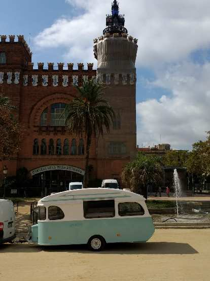 A teal and white trailer in front of a fountain and the Castell de Tres Dragons at the Parc de la Ciutadella in Barcelona, Spain.