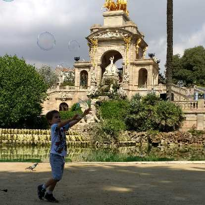A kid trying to catch a huge bubble in front of the Cascada Monumental at the Parc de la Ciutadella in Barcelona, Spain.
