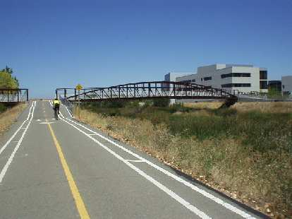 [Mile 99, 12:58 p.m.] A cyclist approaches a bridge on a bike path in Milpitas.