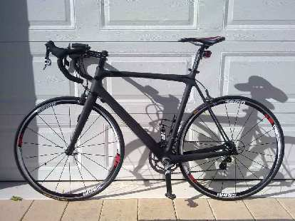 A open-mold Chinese carbon bike painted matte black.