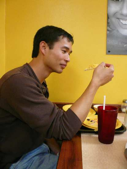 Felix Wong trying the macaroni and cheese pizza.