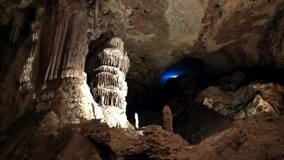 Below the blue light is a large pile of bat dung inside the Blanchard Springs Caverns.