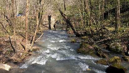 Water gushing from the Blanchard Springs through a circular hole in a pedestrian bridge.