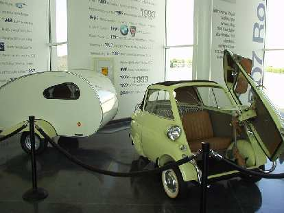 An Isetta with a trailer in tow, as if the Isetta actually had enough power to tow it.