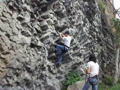 Felix Wong gives the 5.11a a try while Caesar belays.
