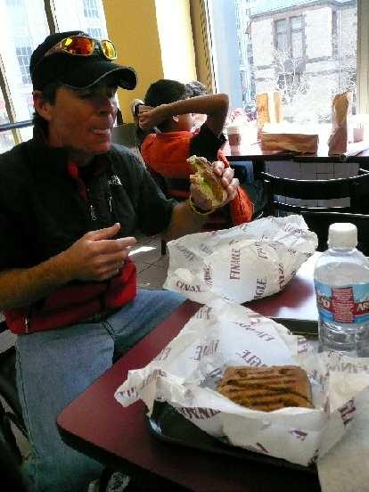 Eddie eating a sandwich at Finnagle A Bagel.