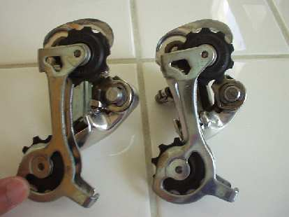 I was riding off-road (on my road bike, and a long piece of barbed wire got tangled in the rear wheel, seizing the wheel.  When the wheel seized, the tension tab on the rear derailleur (Campagnolo Veloce, above right) broke off. (On the left is an identical, unbroken derailleur for comparison.)
