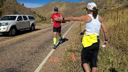 Bob Kennedy, the organizer and oldest finisher of the 2016 Cache La Poudre Marathon, being greeted by Connie DeMercurio as he crosses the finish line.