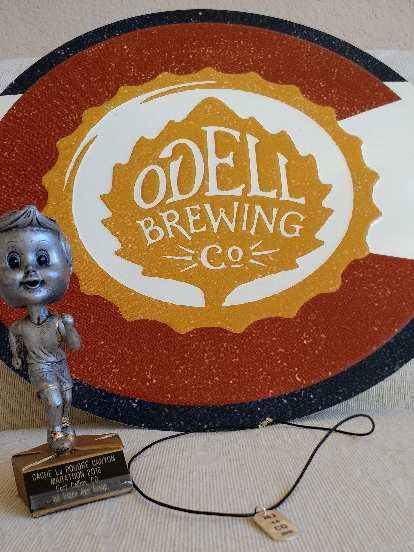 grey bobblehead figure trophy, Odell Brewing Co. placard, necklace with sterling silver pendant