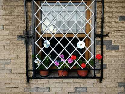 CDs upcycled as art and flowers in a window in a town west of Santander, Spain.