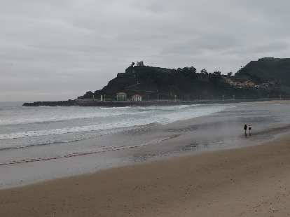 A couple walking along the beach along Punta del Arena in northern Spain.