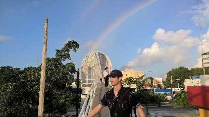 Felix Wong, black shirt, blue cap, rainbow, central Cancún, sunny morning