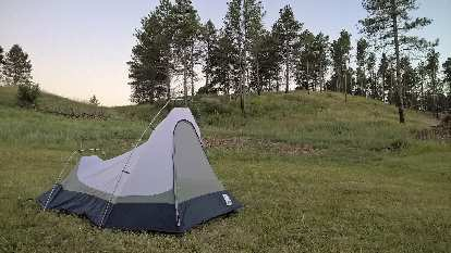 White and blue Sierra Designs Clip Flashlight CD tent, grass, pine trees, Chadron State Park.