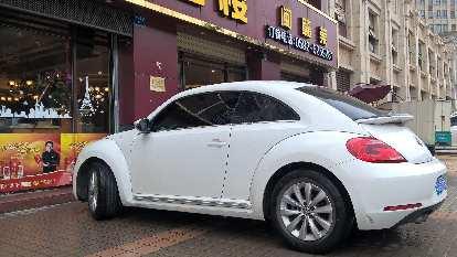 A white Volkswagen Beetle in Xiamen, China.