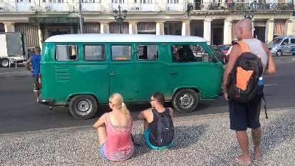 A green 1960s Volkswagen Bus with white top in front of Hotel Inglaterra in Havana, Cuba.