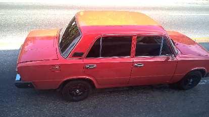 "A red/orange Lada sedan with Honda ""Type R"" logos as seen east of Havana, Cuba."