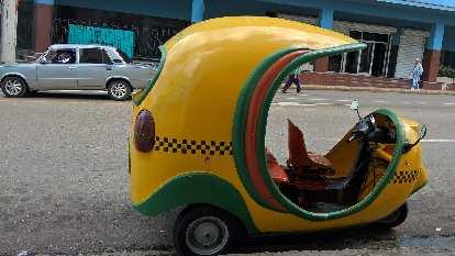 A yellow/green three-wheeled taxi in Havana, Cuba.