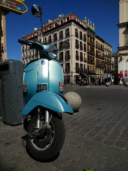 The front of a teal Vespa in Madrid.