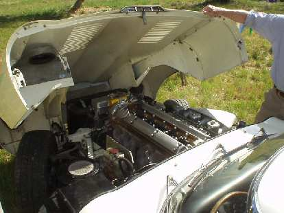 Under the bonnet of the E-type, you can see the massive inline-6 with no less than 3 SU carburetors.