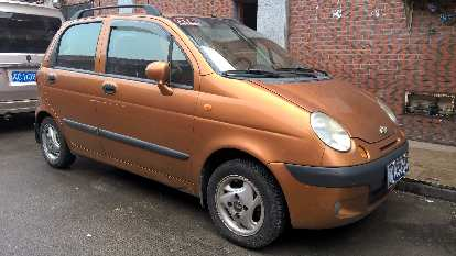 A bronze Chevy Spark in Licheng, China.