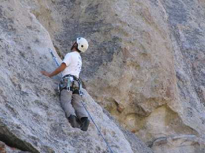 Felix Wong scanning the rock above and pondering his next move after clipping a bolt.