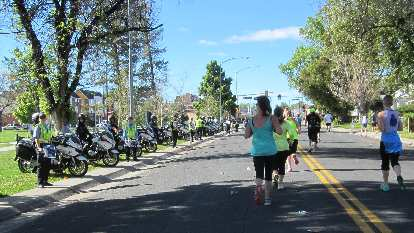 Police officers and motorcycles lining the 2015 Colfax Half Marathon course, runners