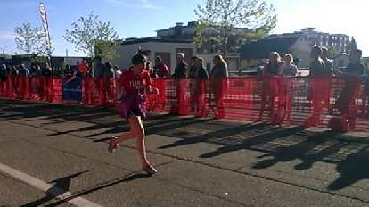 Maureen running in the final stretch of the Colorado Marathon 10k, red shirt, Team Beef