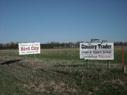 """Welcome to the only Bird City in America.""  Also an ad for a gun & pawn shop."