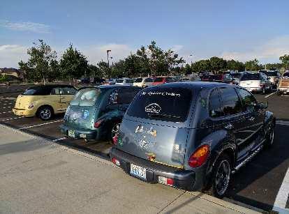 "A yellow PT Cruiser Convertible, a green ""Silver Surfer"" PT Cruiser, and a Mt. Rainier ""OZCRUSR."""