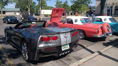 A grey seventh-generation Corvette convertible with two 1950s-era Ford Thunderbirds.
