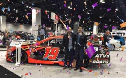 Manuel and Felix with a Toyota NASCAR race car.