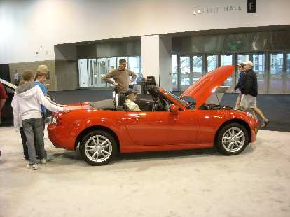 An orange-red Mazda MX-5, Leah's favorite car of the show.