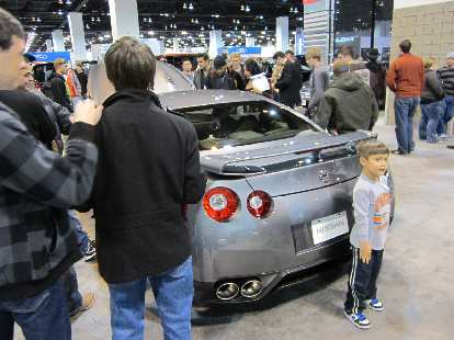 Kid obscuring the rear of the Nissan GT-R (supposedly capable of 0-60 in 2.6 seconds).