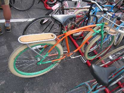Orange and green cruiser with wooden rear rack.