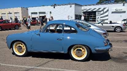 A blue 1965 Porsche 365 with yellow rims.
