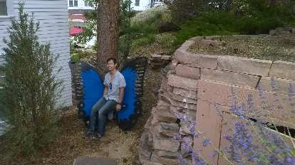 Felix Wong on a blue butterfly bench outside the Stanley Hotel.