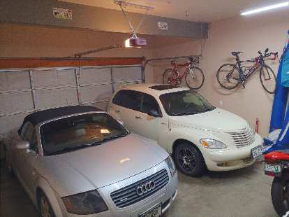 silver Audi TT Roadster Quattro and white 2005 PT Cruiser GT with two bicycles in garage