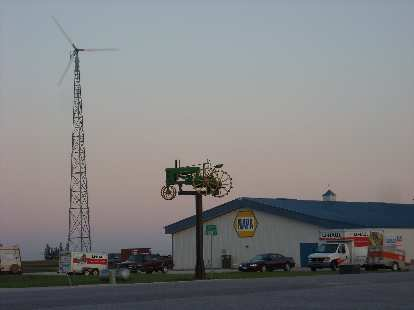 A windmill and lawn tractor by a Napa Auto Parks store not too far from Des Moines, Iowa.
