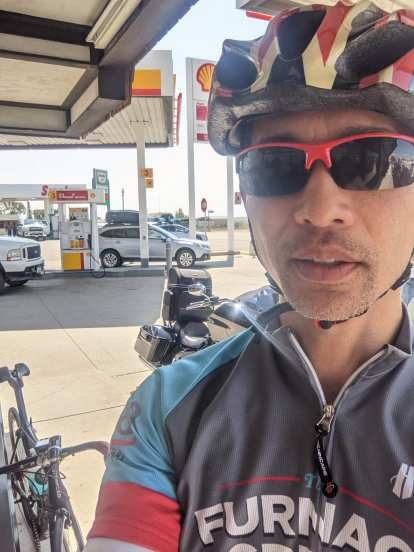 Felix Wong wearing grey/turquoise/red Furnace Creek 508 bicycle jersey, red sun glasses, with carbon fiber bicycle and cruiser motorcycle outside Shell gas station