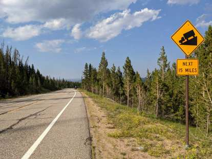 """Yellow sign that says """"Downhill next 15 miles"""" heading east from Cameron Pass on Highway 14 in Colorado"""