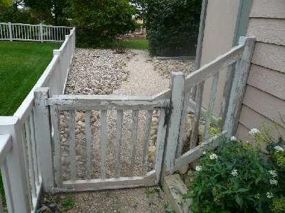 """An """"before"""" shot of the front of the side gate and fence."""